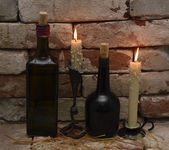 Burning candles with black bottles — Stock Photo