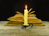 Burning candle with pile of books — Stock Photo
