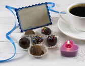 Coffee cup with chocolate candies, candle and card — Stock Photo