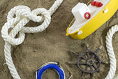 Toy boat and sea objects on sand — Stock Photo