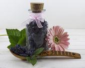 Bottle with honeysuckle berries — Stock Photo