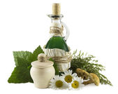 Glass bottle with herbs — Stock Photo