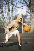 Portrait of a hooded basketball player dribbling the ball — Stock Photo