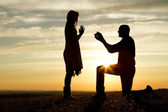 Sunset silhouette marriage proposal — Stock Photo