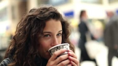 Attractive young woman taking time out and enjoying a hot drink whilst smiling to herself — Stock Video