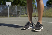 Close up of male feet standing on an outdoor basketball court with a skipping rope on a bright sunny day — Stock Photo