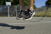 Close up of male feet jumping in the air whilst using a skipping rope — Stock Photo