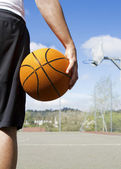 Basketball player holding  a ball close up — Stock Photo