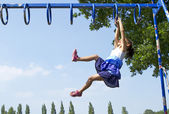 Young girl playing on monkey bars in an outdoor playground on a bright sunny day — Stock Photo