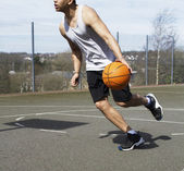 Basketball player dribbling the ball — Стоковое фото