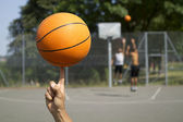 Basketball spinning on a finger — Stock Photo