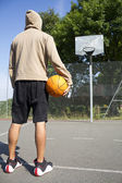 Hooded basketball player standing on a court looking towards the hoop — ストック写真