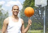 Portrait of a smiling basketball player spinning a ball towards camera — Stock Photo