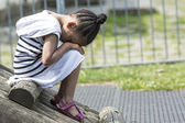 Young girl sitting in a playground with her head on her lap as she is sad — Stock Photo