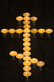 tea lights in the shape of a Orthodox cross on wood background — Stock Photo