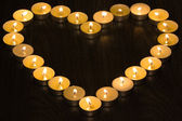 Tea candles in the shape of a heart on wood background — Stock Photo