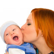 Happy family. A young mother is kissing baby. — Stock Photo