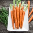 Baby carrots on a white plate — Stock Photo #48834817