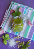 Green pesto in a glass jar and ingredients — Stock Photo