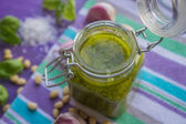 Green pesto in a glass jar and ingredients — Foto de Stock