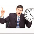 Businessman holding wall clock — Stock Photo