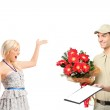 Delivery boy delivering a bunch of flowers and surprised woman — Stock Photo #45856377