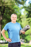 Mature man holding exercising mat — Foto de Stock