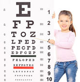 Girl pointing at an eyesight test — Stock Photo