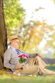 Senior with flowers checking time — Stock Photo