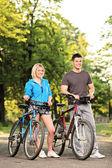 Smiling couple with bikes — Stock Photo