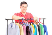 Guy on hang rail full of clothes — Stock Photo