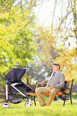 Senior man looking at nephew in stroller — Stock Photo