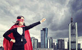 Female superhero standing in front of a city  — Stock Photo