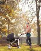 Mother with baby stroller — Stock Photo