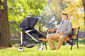 Grandfather looking at nephew in stroller — Stock Photo