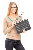 Young woman holding a movie clap  — Stock Photo