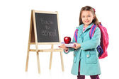 A child next to a school board holding books and red apple — Stock Photo