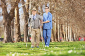 Gentleman and a male nurse  in park — Stock Photo