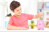 Boy inserting coins into piggybank — Foto Stock