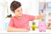 Boy inserting coins into piggybank — Stock Photo