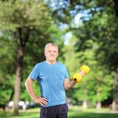 Mature man exercising with weight — Stock Photo