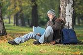 Studentů, sedět na trávě, čtení — Stock fotografie