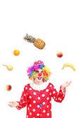 Clown juggling fruits — Stock Photo