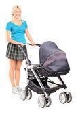 Woman pushing baby stroller — Stock Photo