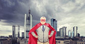 Mature superhero  in front of city — Stock Photo
