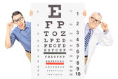 Man and optician behind eyesight test — Stock Photo
