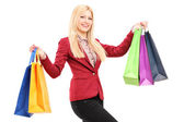 Blond woman holding shopping bags — Foto Stock