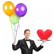 A butler holding balloons and a tray with a heart shape object — Stock Photo #45860541
