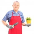 Mature man holding plant and spade — Stock Photo #45862217