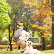 Man reading a newspaper with dog — Stock Photo